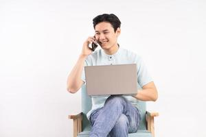 Handsome man with laptop sitting on sofa listening to the phone and working photo