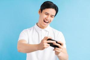 Excited handsome young male gamer playing online game on smartphone isolated on blue background photo