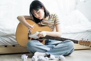 Young Asian girl is practicing guitar at home and composing music photo