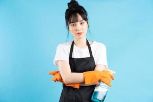 Asian housewife is wearing orange gloves and holding a spray of water in her hand photo