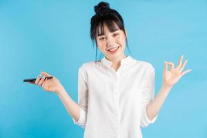 Hermosa mujer asiática sosteniendo el teléfono y usando sus manos para hacer un símbolo ok foto