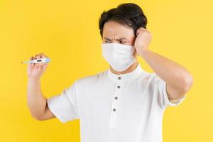 Young man wearing a mask, holding a thermometer, and feeling a headache photo