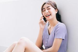 Beautiful young Asian woman using smartphone at home photo
