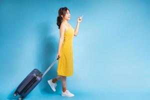 Young Asian woman holding suitcase on blue background, summer concept photo