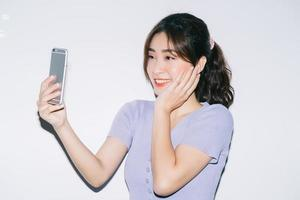 Young Asian woman using smartphone on white background photo
