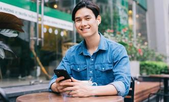 Young Asian man using smartphone at coffee shop photo