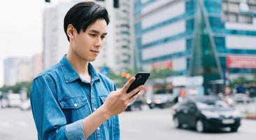 Joven asiático caminando y usando el teléfono inteligente en la calle foto