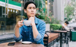 joven asiático está sentado pensativamente mientras bebe café foto