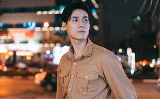 Asian man is walking in the street at night feeling lost photo