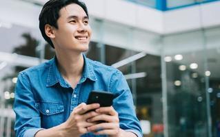 Imagen del joven asiático sonriendo y con smartphone foto