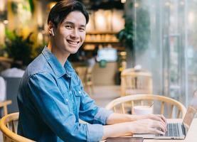 Asian man sitting using laptop in coffee shop photo