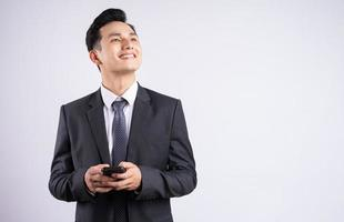 Image of young Asian businessman wearing suit on white background photo