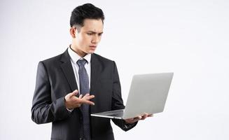 Young Asian businessman using laptop on white background photo