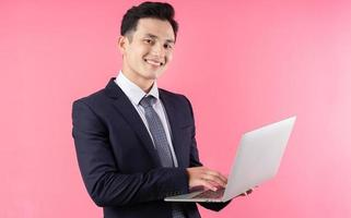Image of young Asian businessman on pink background photo