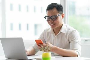 Young Asian businessman using smartphone and laptop at office photo