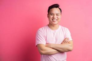 Asian man standing with folded arms on pink background photo