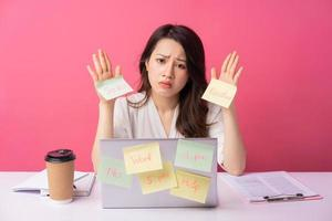 Young Asian businesswoman sitting working with expression on background photo