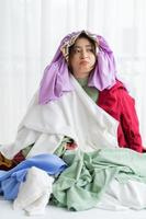Asian girl stuck in her mess of clothes photo