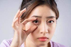 la joven asiática estaba abriendo los ojos con la mano foto