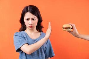 joven mujer asiática renunciando al hábito de comer hamburguesas foto