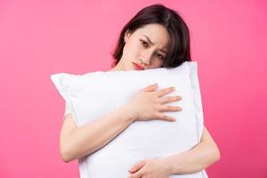 Asian woman is hugging pillow on pink background photo