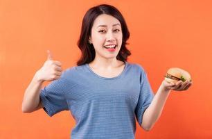 Joven mujer asiática comiendo hamburguesas sobre fondo naranja foto