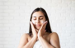 Happy beautiful woman wearing bath robes applying facial cream on her face photo
