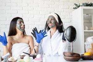 two beautiful women in gloves applying facial mask having fun photo