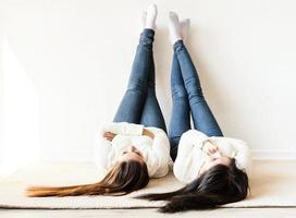 Two women laying at the rug legs up having fun photo