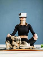 Young woman in sport clothes wearing virtual reality glasses sitting on fitness mat with dog photo