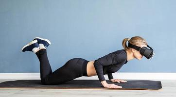 Young blonde woman wearing virtual reality glasses doing push ups at home photo
