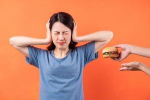 joven asiática está tratando de dejar el hábito de comer hamburguesas foto