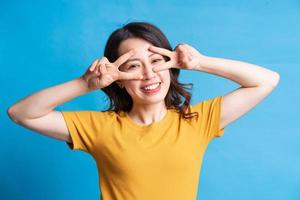 la hermosa mujer asiática está formando un símbolo de paz con su mano foto