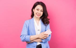 Image of Asian businesswoman on pink bakcground photo