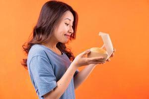 Joven mujer asiática unbox caja de hamburguesas sobre fondo naranja foto