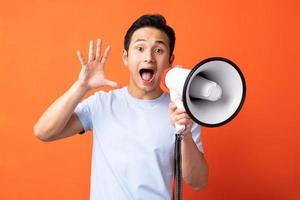 Asian man holding megaphone and shouting photo