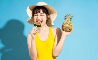 Hermosa mujer asiática vistiendo un mono amarillo sobre fondo azul y comiendo frutas tropicales, concepto de verano foto