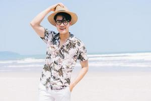 Young Asian man walking on the beach photo