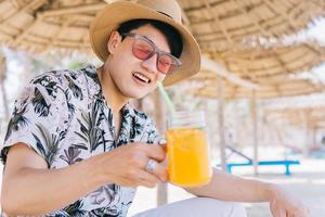 Young Asian man drinking orange juice on the beach photo
