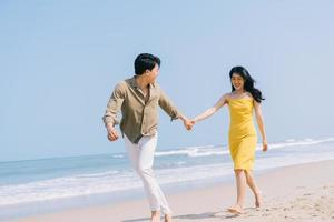 Young Asian couple enjoying summer vacation on the beach photo