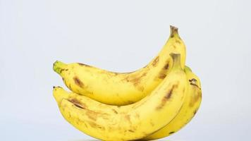Closeup group of ripe yellow bananas rotating 360 degrees on white background. video