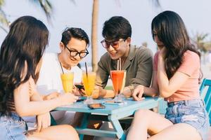 A group of young Asians enjoy a trip to the sea on a summer vacation photo