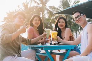 un grupo de jóvenes asiáticos disfrutan de un viaje al mar en unas vacaciones de verano foto