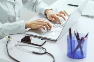 Asian female doctor working with computer in office photo