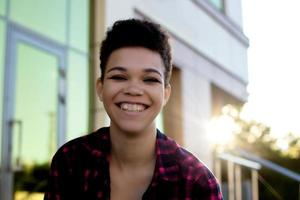 Beautiful African American woman with short hair in the summer on the street photo