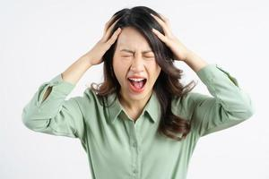 Portrait of a beautiful Asian businesswoman holding her head and screaming photo