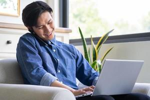 Young Asian man is calling while using computer photo