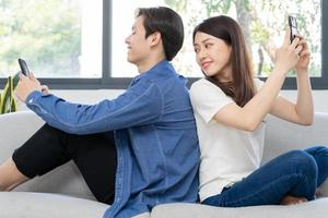 Young Asian couple sitting with their backs on each other and using the phone on the sofa, the girl peeking at her boyfriend's phone photo
