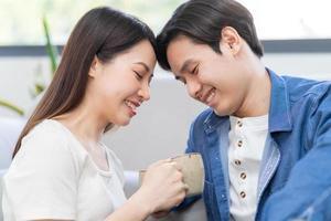 Young Asian couple enjoying tea together photo