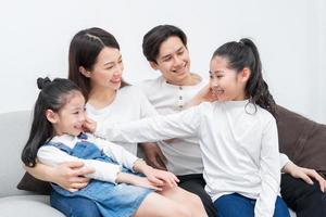 Young Asian family entertained at home in free time photo